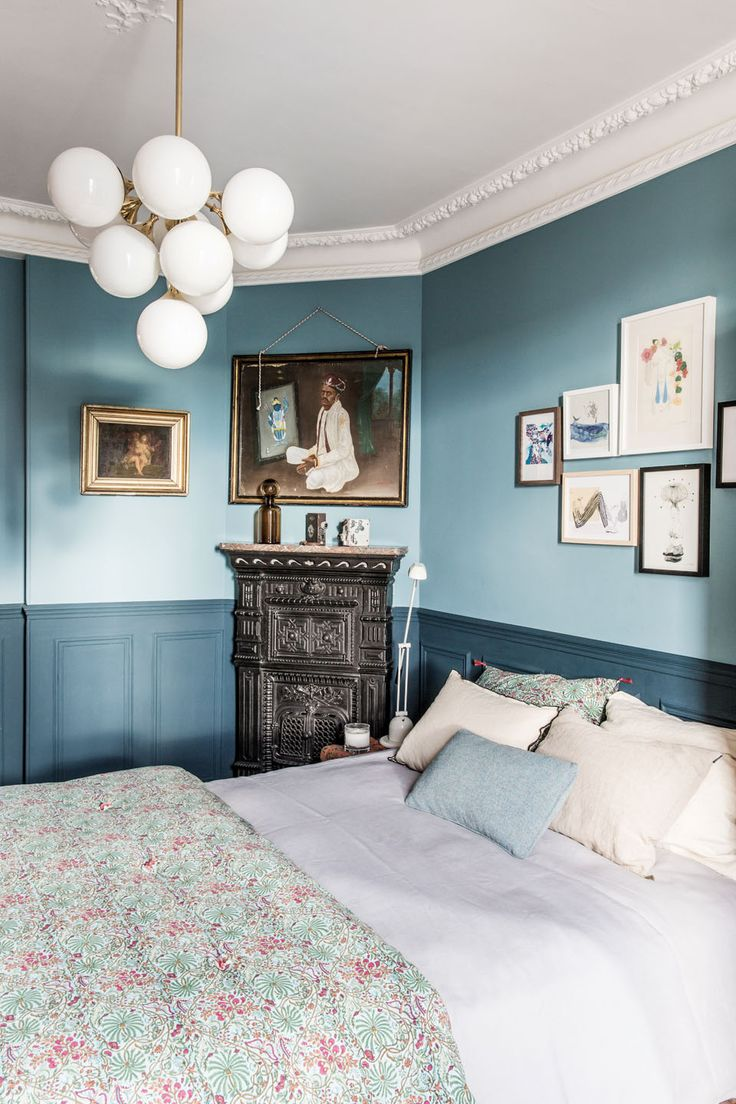 Blue bedroom with modern light fixture, children's drawings above bed and antique fireplace with art above it