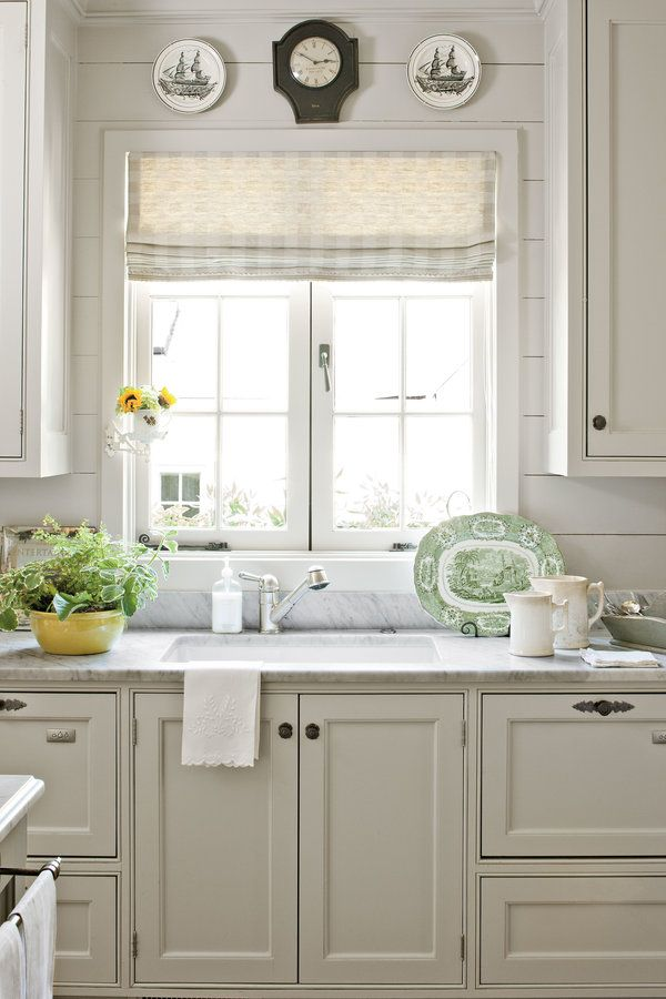 Roman shades, push-out casement windows, marble counter tops and planked walls make for a vintage style kitchen.