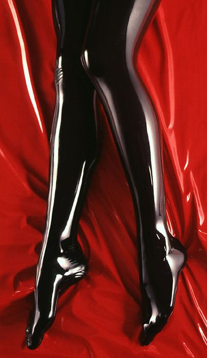 legs in black latex on red sheets
