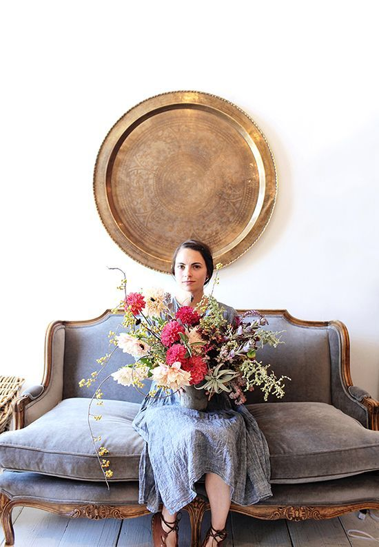 Vintage blue gray couch + brass plate decor with large red + cream wildflower bouquet