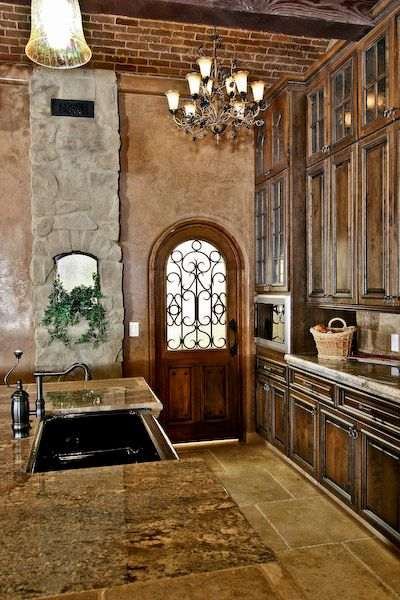 I love all the texture, stone, brick, distressed plaster, arched door with iron scrollwork, wood beams & distressed knotted wood cabintry... Everything I want in a house. Right here.