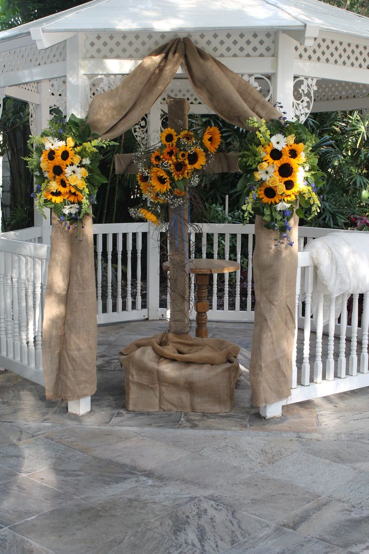 Burlap, sunflowers and gerberas decorate cross and gazebo