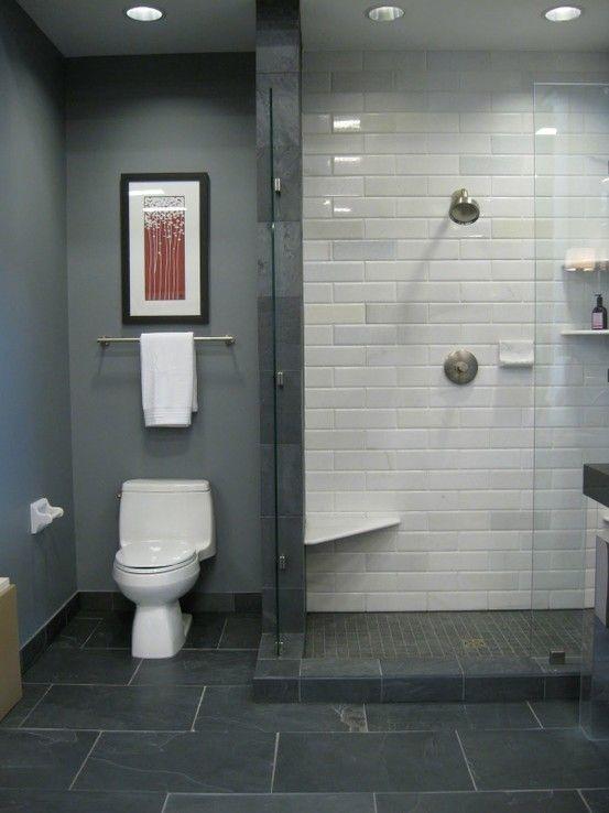 Standing Shower..no sliding door. stationary door. ledge with tile floor. slate tiles in a grey monochromatic bathroom