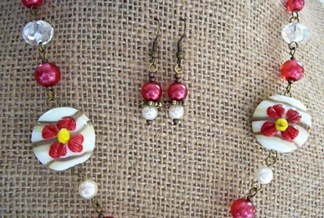 Hravé mohutnejšie ručné vinuté sklo so zdobením 3D kvetiny, doplnené tón v tóne perlami v červenej perleťovej polopriesvitnej a plnej perleťovej bielej farbe a väčším brúseným sklom v tvare donutu s krásnymi odleskami :).  K náhrdelníčku patria aj jemné náušničky z rovnakého materiálu!