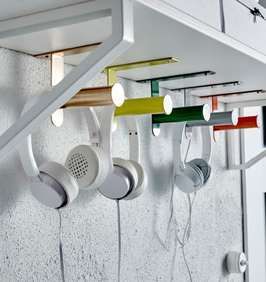 Five IKEA GRUNDTAL toilet roll holders are mounted to the underside of a shelf, and used to hang headphones.