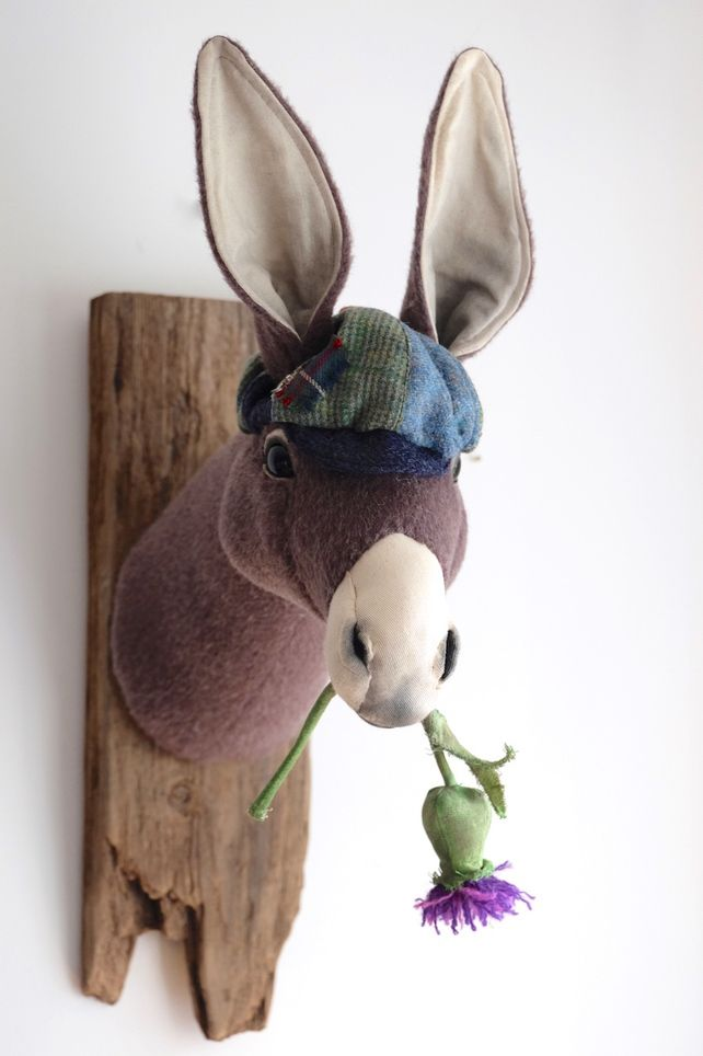 Textile donkey munching thistle fabric sculpture. Vegetarian animal art trophy.