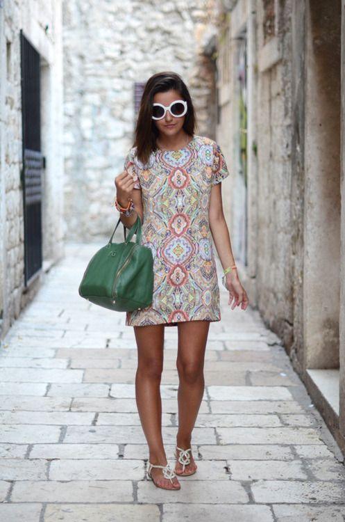 Vestido de colores, bolsa verde, lentes blancos y sandalias.