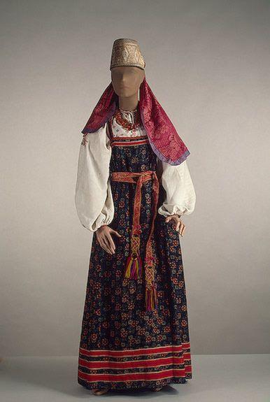 Костюм женский: сарафан, пояс, рубаха, повязка, ожерелье Архангельская губерния. Вторая половина 19 в. Набойка по холсту, кумач, полотно, шелковая лента, цветная нить, галун, янтарь; шитье, набивка, огранка.