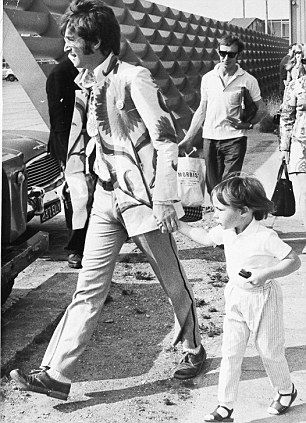 John Lennon pictured with his son Julian on another of their holidays, this time at Heathrow Airport preparing to leave for Greece