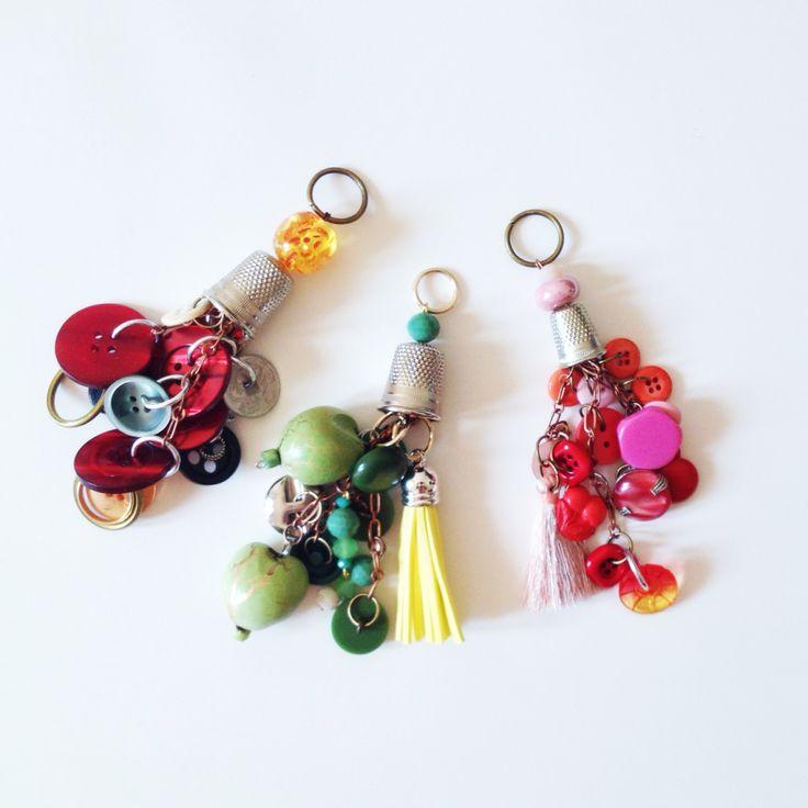 Amuleti multicolor realizzati con bottoni vintage, nappe e coralli in vetro.
