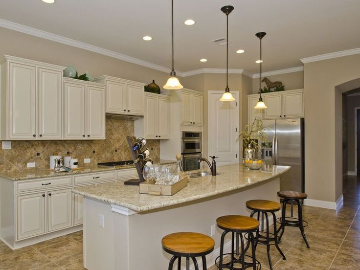 Kitchen With Cream Colored Multi Level Cabinetry With Travertine Tiles And  Cream Colored Granite Counters With Stainless Steel Appliances.