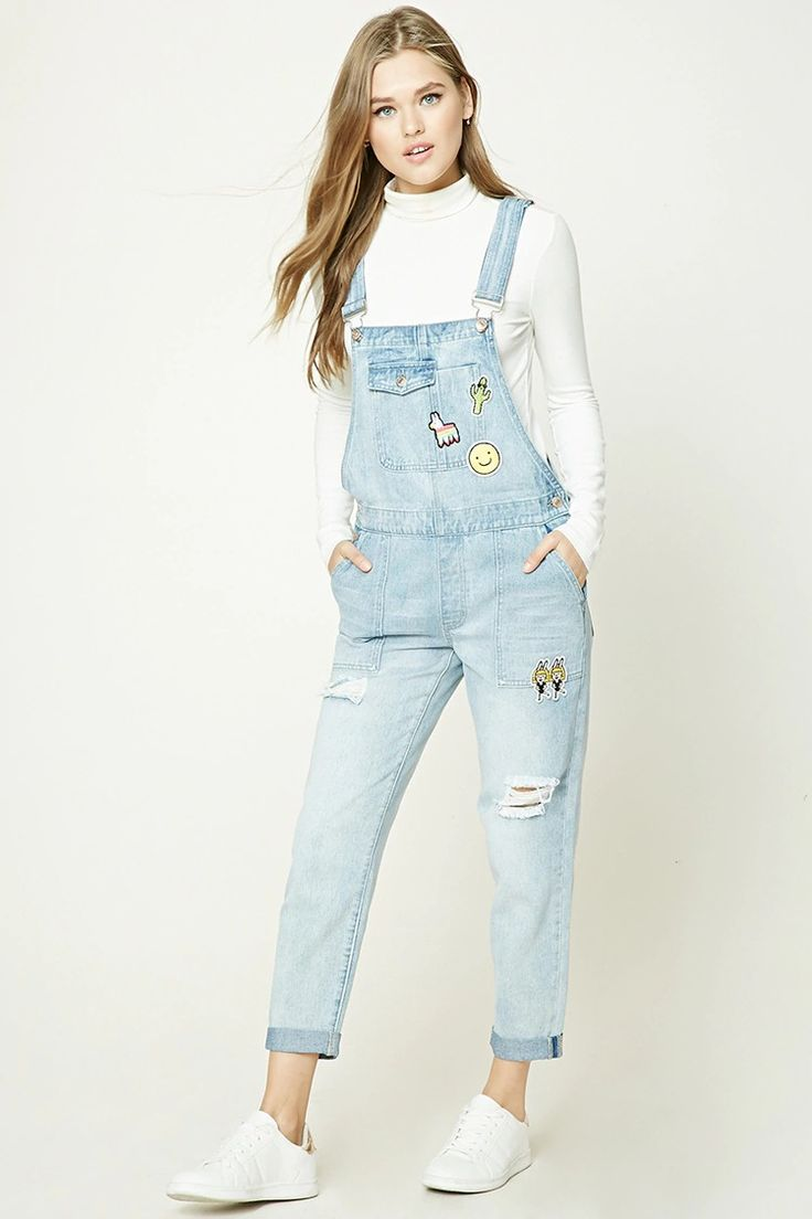 A pair of denim overalls featuring piñata, cactus and happy face patches, a six-pocket construction, adjustable straps with slide-lock closures, distressed knees, and a straight leg fit with cuffed ankles.