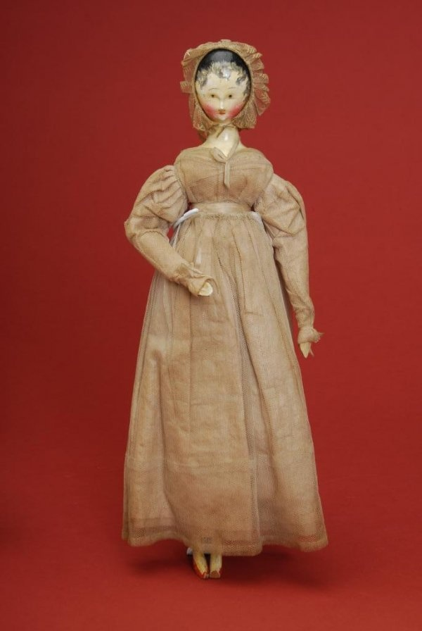 "Austria, ca. 1830, early jointed wooden doll, black painted hair with finely painted tendrils and molded ears, painted facial features with brown eyes, fully jointed wood body with painted lower legs and arms. Wearing original polished cotton dress with net overlay and matching bonnet. Provenance: Estelle Winthrop Collection 12.5"" H"