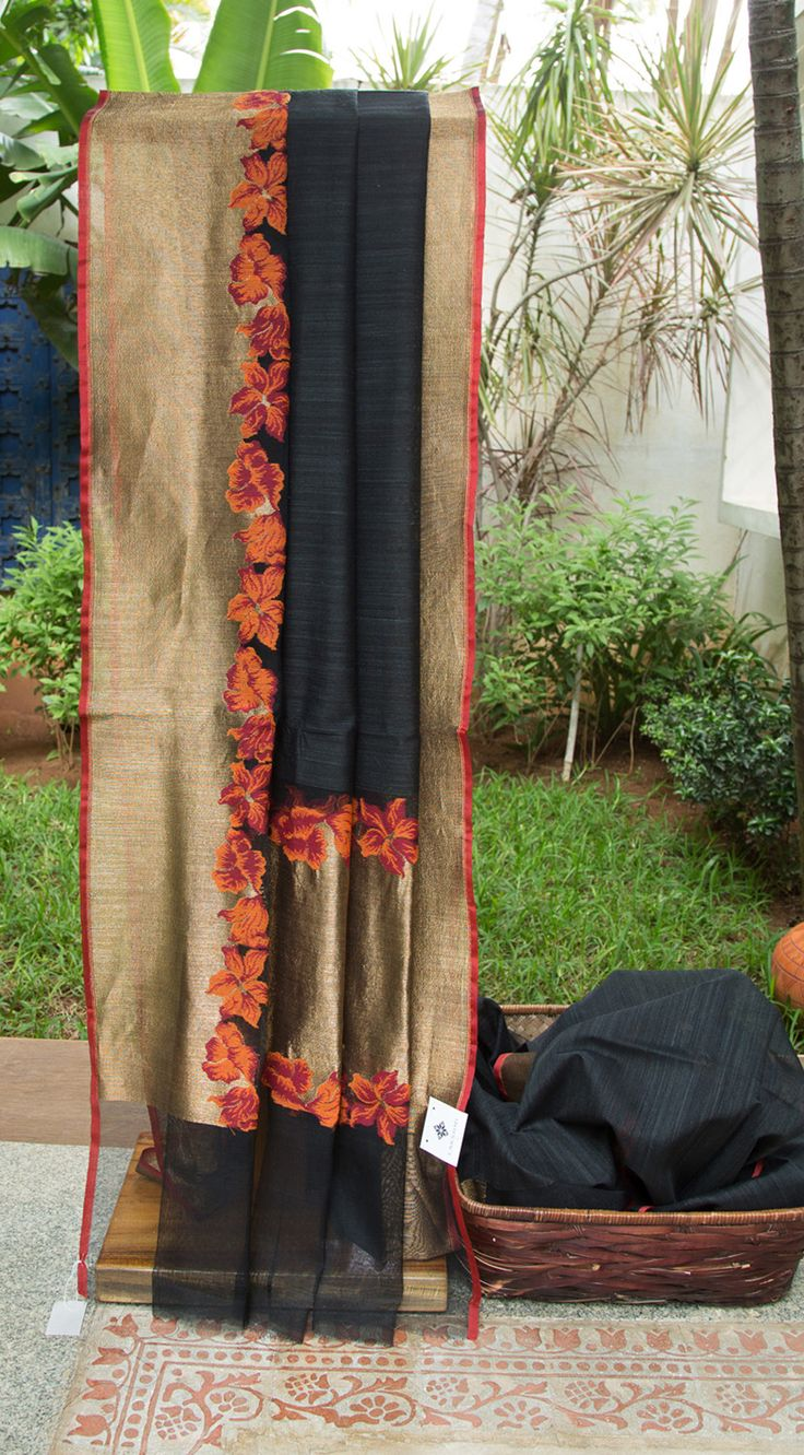 This striking black sari is a handcrafted benares net sari. The border and the pallu have solid gold zari texturing along with a floral pattern at the edging in currant red and tiger orange thread …