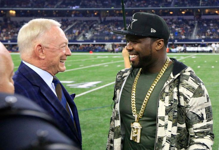Dallas Cowboys team owner Jerry Jones, left, talks with rap artist 50 Cent, right, before an NFL football game against the Chicago Bears, Sunday, Sept. 25, 2016, in Arlington, Texas.