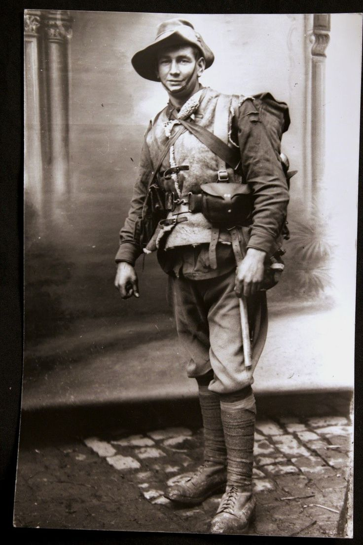 Photo of an unknown Australian soldier standing on muddy cobblestones before a studio background in Vignacourt, France, December 1916. Note the torn unit colour patch on his left arm.