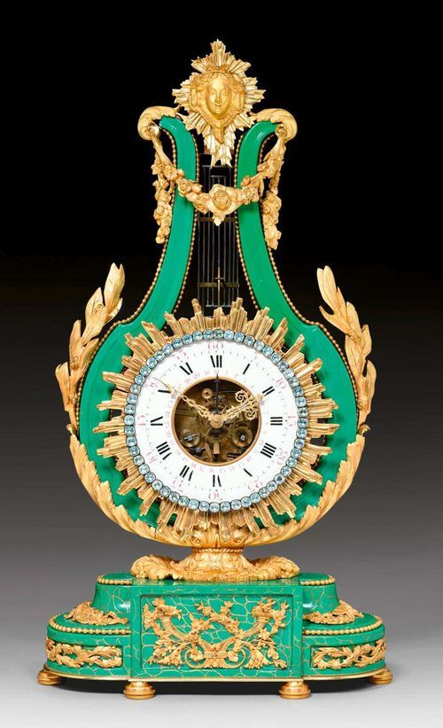 LYRE CLOCK WITH GREEN PORCELAIN,late Louis XVI, the porcelain from the Manufacture de Sevres, Paris, 19th century. Green porcelain with parcel gold craquelure. Enamel chapter ring with paste stone edging. Fine skeleton movement striking the 1/2 hours on bell. Exceptionally fine, matte and polished gilt bronze mounts and applications. 34x14x61 cm. Provenance: - Former collection of Duesberg, Mons. - Swiss private collection.