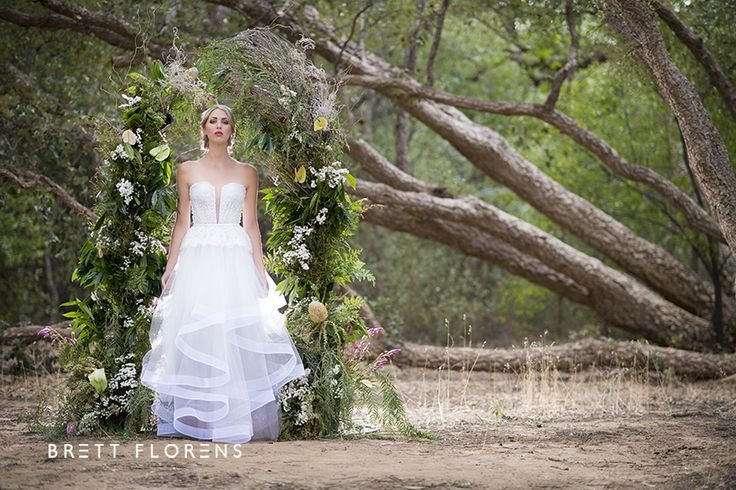 Brett Florens   Lourensford – KADOU   Oversized arch in between beautiful cork trees with wedding dresses, bouquets and candlelights.