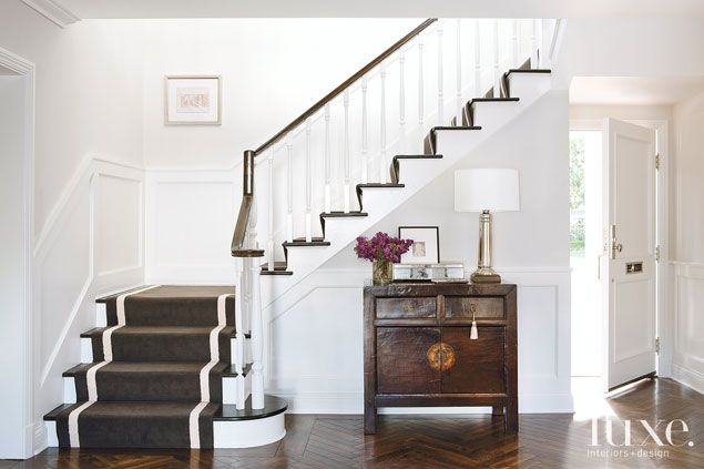 Cari Berg designed interiors with a contemporary feel to complement the traditional architecture. In the foyer, she lined the stairway with ...