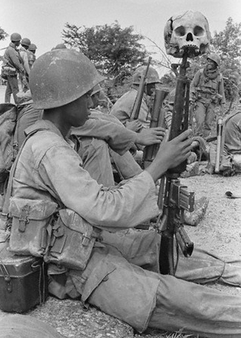 A soldier in Cambodia resting with a skull on his rifle. September 05, 1973