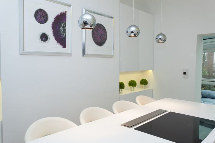 The silver, ceiling lights add a quirky style and a pop of colour to the pristine white kitchen. The art frame on the opposite wall features a simple design, complementing the pendant lights. #kitchen #kitchenstyle #kitchendesign #modernkitchen #contemporarykitchen #kitchenlights #interiordesign