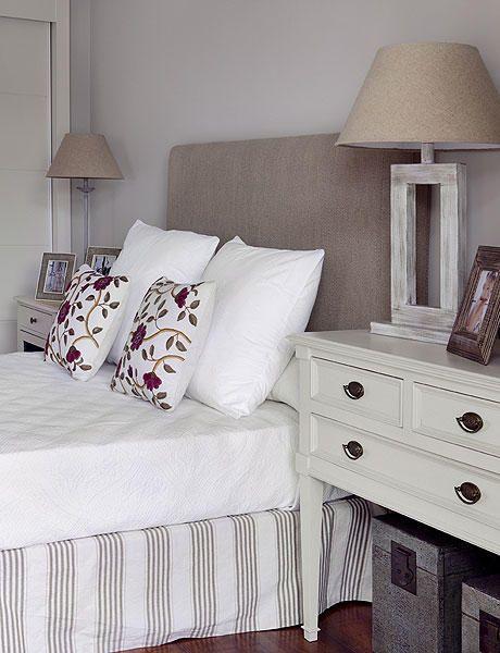 Cabecero liso en tono tierra con lámparas a juego. Ropa de cama en blanco.