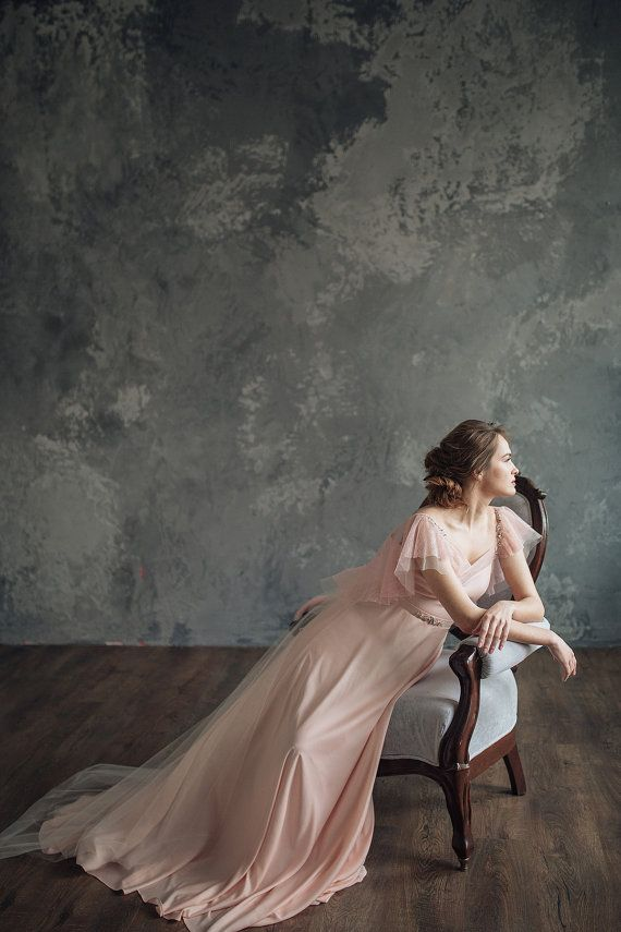 This is the romantic wedding dress with flounces on the back. Top part of the dress is made of a base of soft stretch silk and delicate french lace light pink color. The flounces lace and tulle are located on the back V-shaped top offers a flattering neckline with playfully draped back. Its skirt is made using stretch silk blush pink color and tulle only back to the floor – light peach color. Everywhere lining of the peach-colored. The dress has left side closure with invisible zipper and…