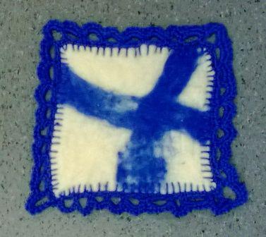 Huovutettu pannulappu 3 lk Reunaan on ommeltu pykäpistoja villalangalla ja samalla värillä harjoiteltu virkkausta pykäpistoihin.