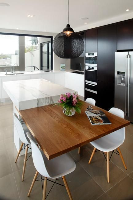 Modern kitchen with timber dining table attached to the island bench. For similar pins please follow me at - https://www.pinterest.com/annelouise1959/kitchen-glamour/