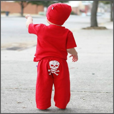 Red 'Skull' Crawler. Your little pirate is ready for some fun in these stretchy, soft play-pants! With a puffy pirate print on the rear, these pants are bold and daring, just like your little guy! These 'crawler' style pants were designed with your little mobile one in mind. In an ankle length style, the soft, stretchy cotton provides gentle protection from carpet burn knees, and makes for the perfect play pant as he grows.