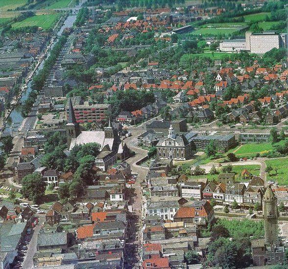 """Luchtfoto uit 1977 met vlnr oa het """"oude"""" Mariënbosch, schouwburg, Crackstate met secretarie, bibliotheek aan de K.R. Poststraat en de watertoren."""