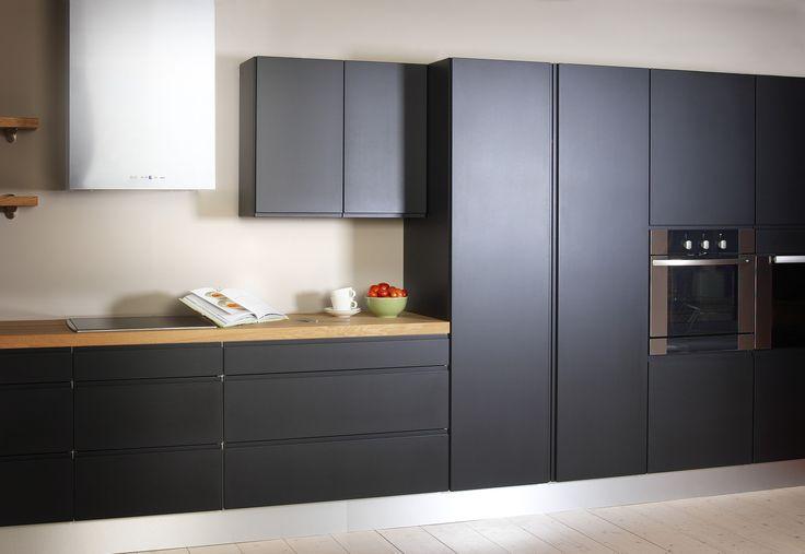 Yhdelle seinustalle rakennettu keittiö. Mustat korkeat kaapinovet ja leveät alakaapit luovat rikkoutumatonta linjaa keittiöön. #puuvaja