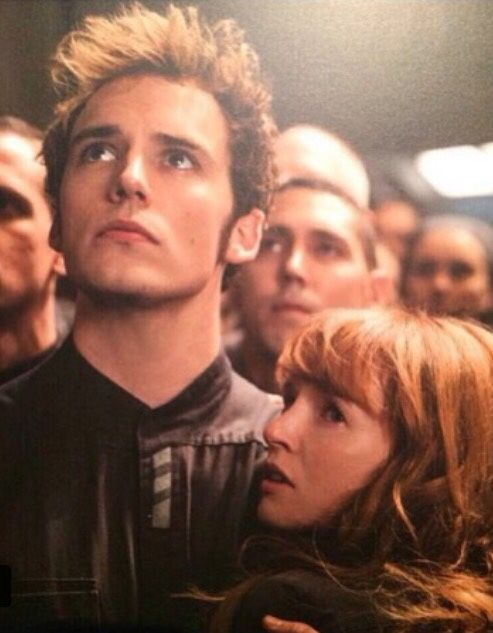 Finnick and Annie in Mockingjay Part One.  They're watching the speech that Coin gives after Peeta, Johanna and Annie were liberated from the Capitol.