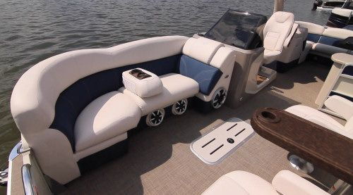 Premier 250 Intrigue: The couches are all remarkably comfortable and floating armrests include drink holders and cargo netting to the sides. Notice the dual speakers and subwoofer underneath. Because there's a center tube Premier was able to accommodate an in-deck storage compartment.