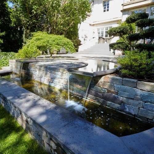 Harmonisches Wasserspiel aus Naturstein Grauwacke der Firma Quirrenbach, klassischer Garten mit wunderschönen Gestaltungsideen. | Rheingrün Gartengestaltung