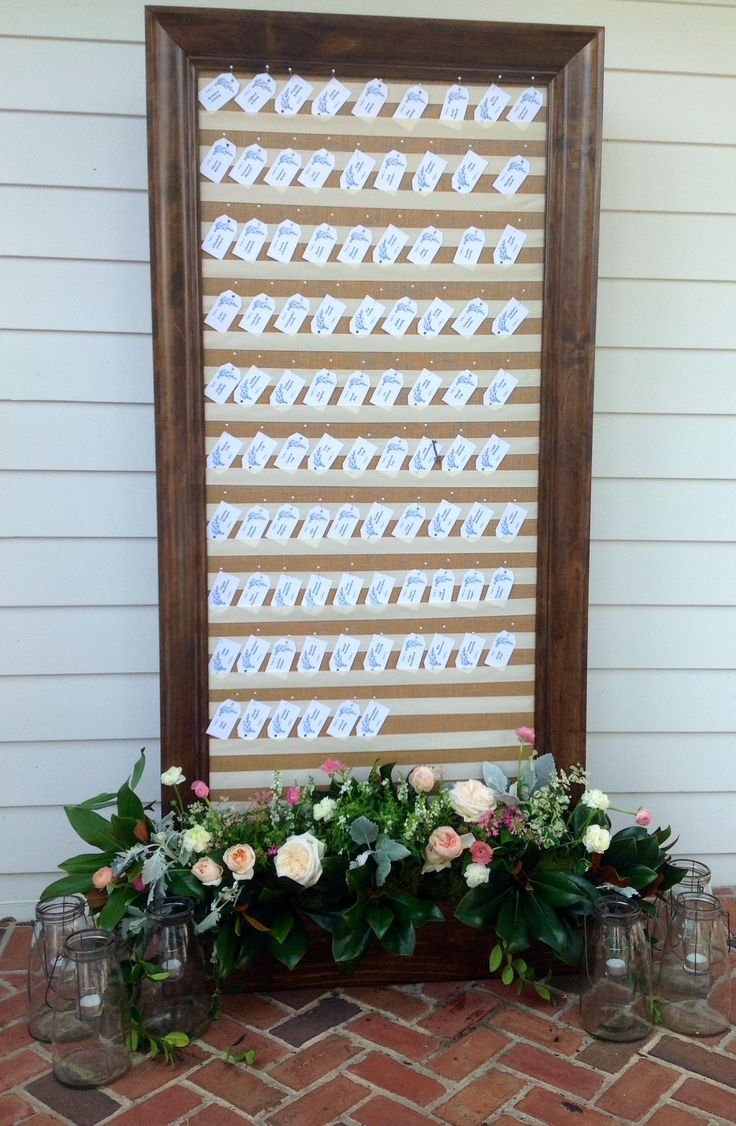 the escort card display board was found on the covered porch of this lakeside estate home- a varnished wood framed board, covered in burlap with rows of cream satin ribbon, with a lusciously overflowing dressing of with juliette garden roses, amelia garden roses, white and pink ranunculus, dusty miller, white angelonia, seeded eucalyptus and lemon leaf.