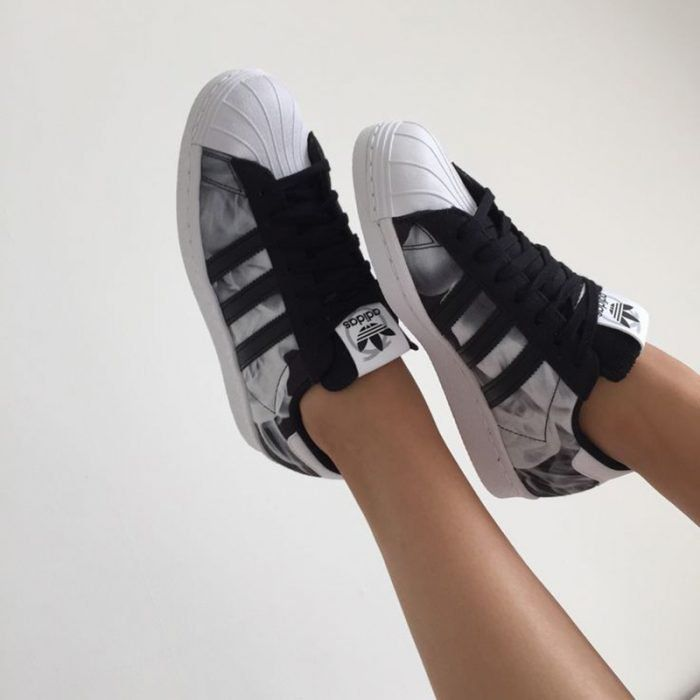 pies de mujer con tenis adidas superstar negro