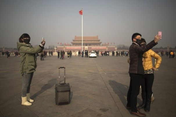 Tourists in masks use cellphone cameras to snap shots of themselves on a heavily polluted day in Tiananmen Square in Beijing.
