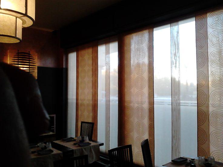 Pannelli scorrevoli che creano un gioco di sovrapposizioni per un effetto di chiaro scuro dettato dalla luce stessa. Sono applicati a soffitto con un classico binario scorrevole a vie indipendenti.  Il tessuto che abbiamo utilizzato è un misto lino di color avorio naturale per i pannelli più trasparenti, un tessuto lucido con un ricamo di cerchi concentrici il tutto in diverse gradazioni di arancio per i secondi pannelli