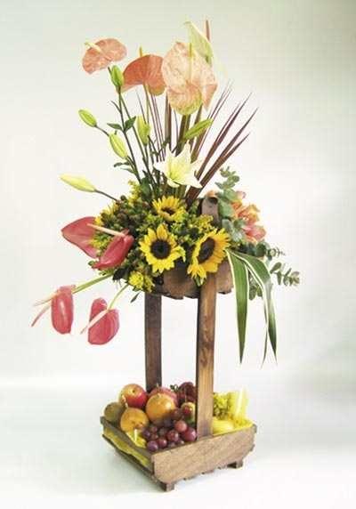Original arreglo mixto de flores y frutas en base con forma de pozo.