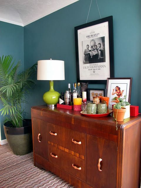 benjamin moore caribbean teal is a popular blue green paint colour.  Shown on vintage buffet in dining room with decor