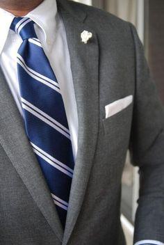 グレースーツに紺のレジメンタルタイ、白チーフを合わせた着こなし