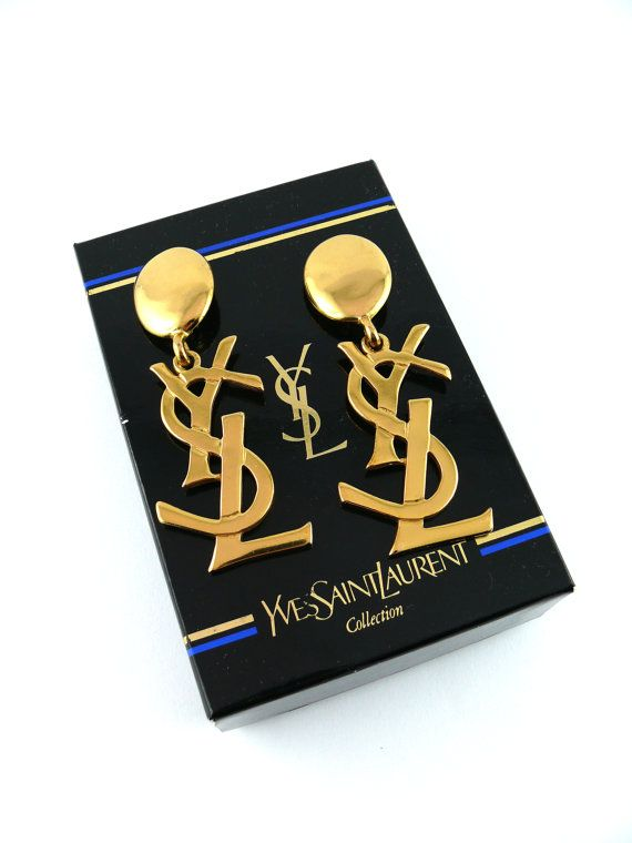 Gorgeous and highly sought-after vintage gold tone iconic logo dangling earrings YVES SAINT LAURENT.  Seen on Samantha Jones (Kim Cattrall) in Sex and the City Marked YSL Made in France on the reverse.  Excellent vintage condition (Grade : A). Minor scratches throughout.  Indicative dimensions (for information purposes only) : - height 8.2 cm (3.23 inches) - width 3.2 cm (1.26 inches)  Comes with original YVES SAINT LAURENT Collection box.  Colors may differ slightly from actual product…