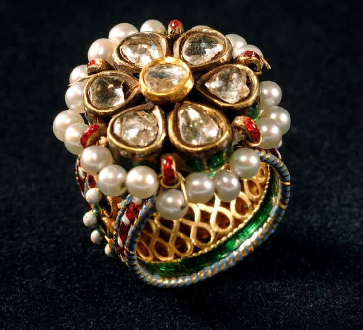 A ring, traditionally part of a 'hadphool', hand jewellery,decorated with multicoloured enamel, set with diamonds and the rim is decorated with pearls.