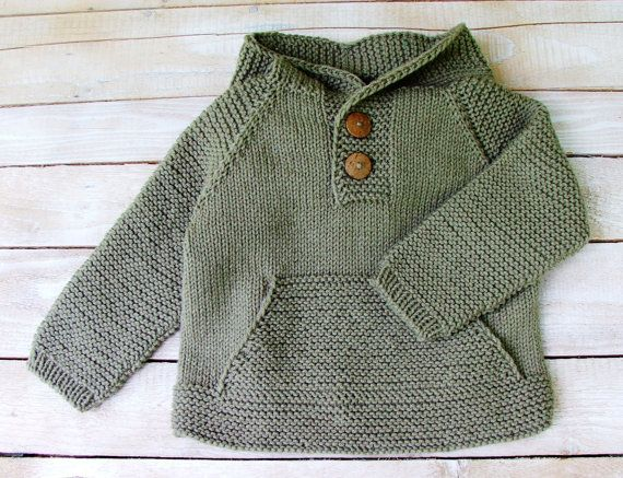 This hooded sweater will fit toddlers up to 3 years old.  Hand knitted from easy care acrylic in a neutral shade of taupe, this hoodie is a modern classic. Features coconut shell buttons and a roomy front pocket, as well as an over-sized hood, and sturdy seamless construction. This sweater will keep any active toddler boy warm and cozy. Sweater measures 15 from shoulder to hem, 14 1/2 across chest, and 15 from neckline to cuff. Machine washable.