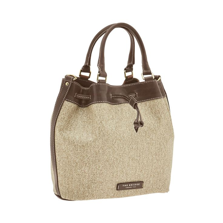 This shopping tote bag from The Bridge features an elegant, practical design. Perfect for travel and leisure. Extremely versatile, it can be worn on a shoulder or carried by its two handles. Leather details add a touch of class and guarantee comfort and durability. Size 32X30X11 cm. #TheBridgeBag