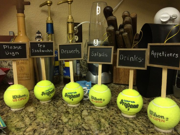 Food/Table markers for tennis themed party. Using inexpensive chalkboard tags from Craft store, hot glue to Popsicle stick. Cut hole on top of clean, used tennis ball. Stick the Popsicle stick label into ball. To keep ball from moving, hot glue a felt pad (the kind used for chair legs for protection).