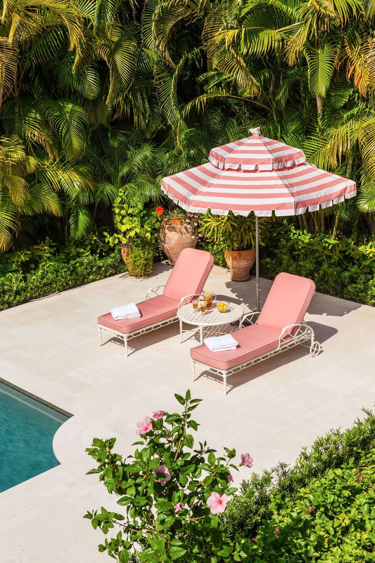 Tropical Gardens | Tropical poolside pink umbrella & chaises with palm hedge backdrop