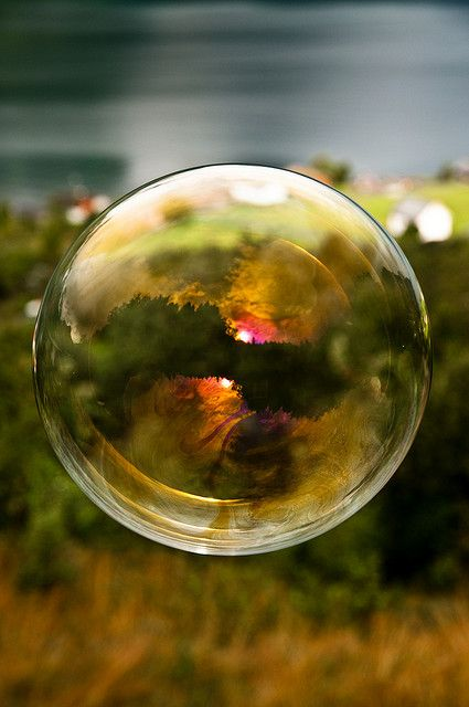 Morning light reflected in a soap bubble over the fjord by Odin Hole Standal