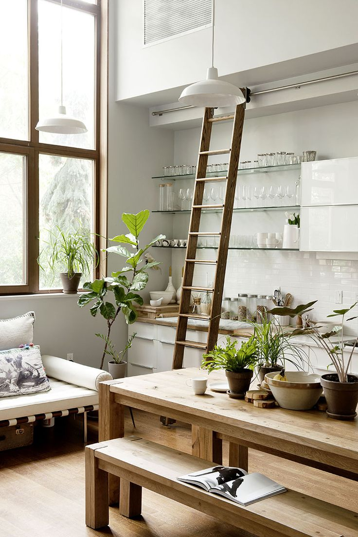 Kitchen with white walls, large windows, white light fixtures, glass shelves, wood floors, wood table, wood bench, white couch, plants, and wood ladder